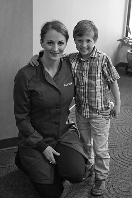 One of Dr. Bova's Mercer Island Dentists team members sitting with a young patient smiling